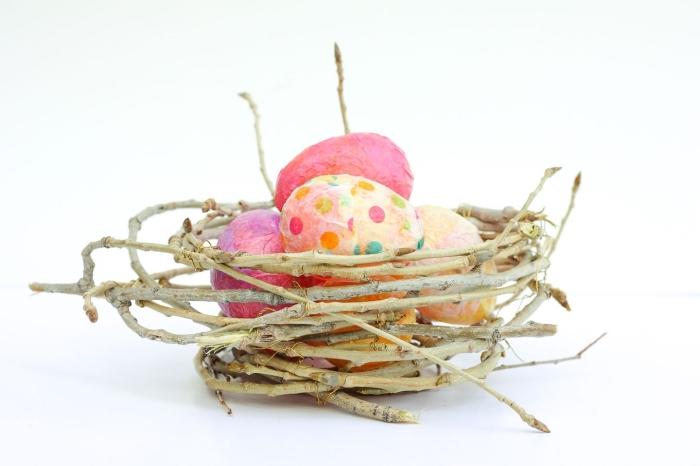 osternest selber basteln, nest aus zweigen, bunte eier dekoriert mit buntem papier