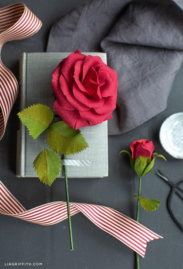 Rote Rosen aus Krepppapier, gestreifte Schleife in Rot und Weiß, Buch als Geschenk schön dekorieren