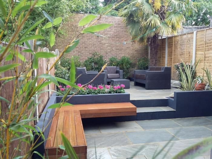 graue Fliesen, zwei Bänke, schwarze Loungemöbel, rosa Blumen, Hoher Sichtschutz, Gartengestaltung Beispiele
