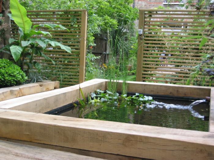 ein Teich mit Wasserspiel, hoher Sichtschutz, frische grüne Pflanzen, Gartengestaltung Beispiele