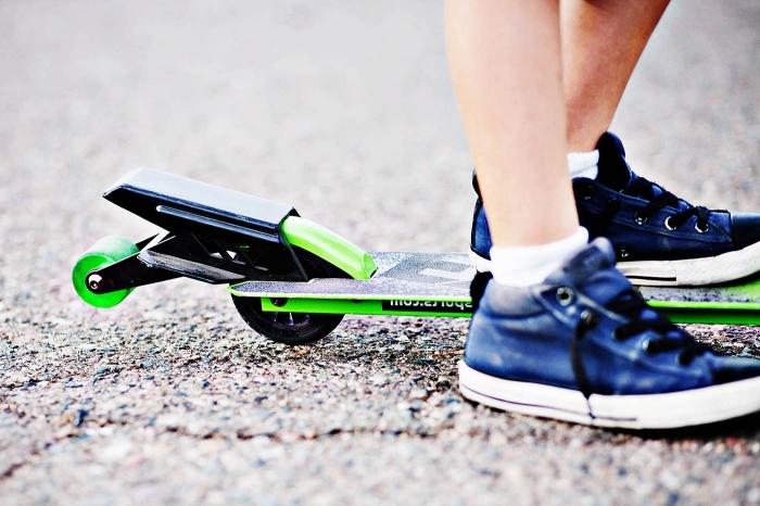 stunt scooter in schwarz und grün, blaue sportschuhe, apshalt, beine