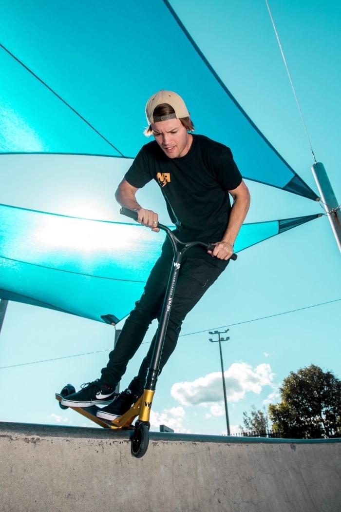 stunt scooter in gold und schwarz, blaues sonnensegel, große rampe, tricks machen