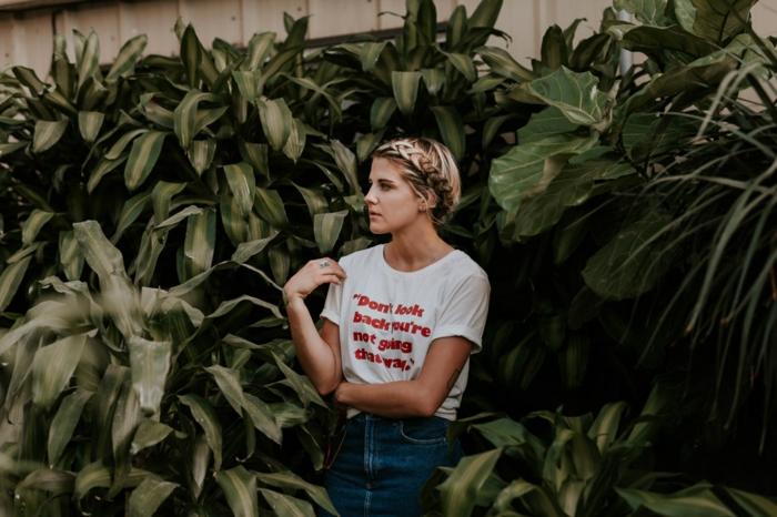 viele grüne pflanzen und eine junge frau mit einem weißen t-shirt