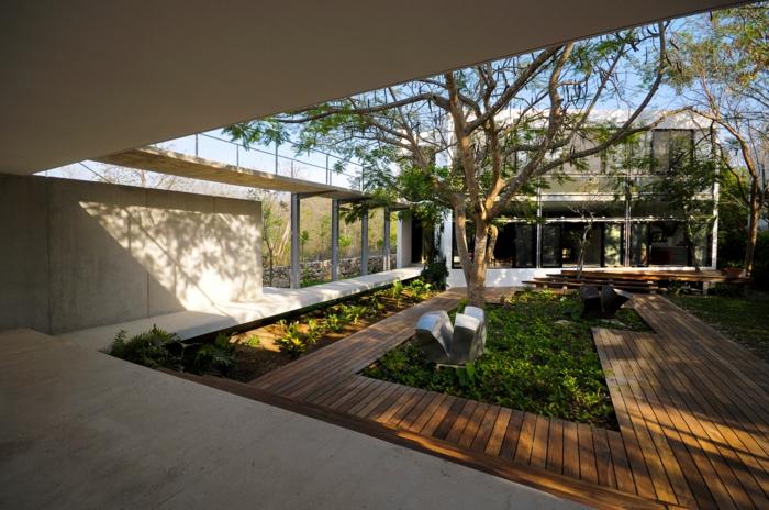 Terrassendiele, grüner Gras, ein hoher Baum, Vorgarten modern, seltsame Skulpturen von zeitgenossischer Kunst