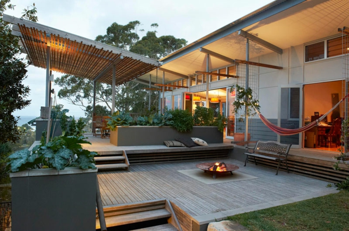ein Pergola, Terrassendiele, ein Hängematte, ein Feuerplatz in der Mitte, Gartengestaltung Beispiele
