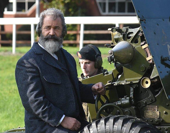 alter mann mit grauen kopfhörern, der schauspieler mel gibson mit einem langen bart und mit langem grauen mantel, the professor and the madman