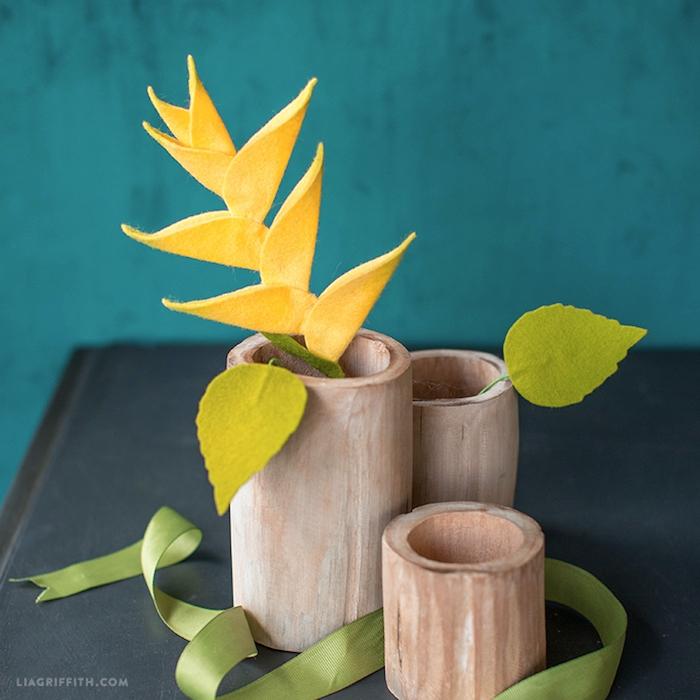Handgemachte Blumen aus Filz in Vasen aus Holz, grünes Dekoband, DIY Dekoartikel fürs Wohnzimmer