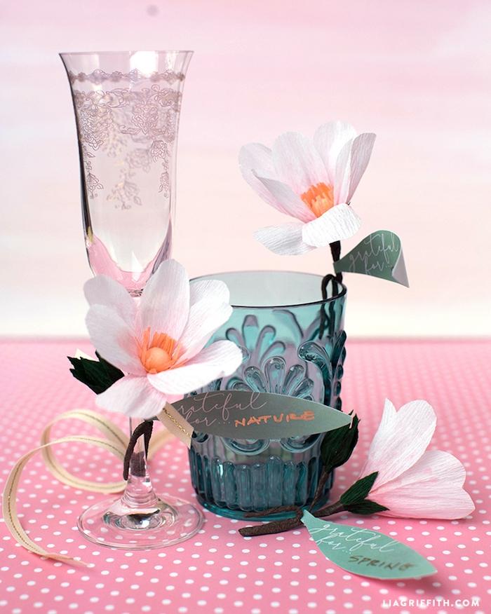 Ideen für selbstgemachte Tischdekoration, kleine weiße Papierblumen an Gläsern befestigen