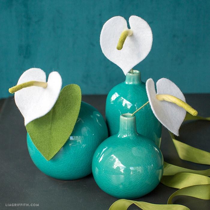 Handgemachte weiße Blumen aus Filz in blauen Vasen, DIY Dekoartikel für Zuhause