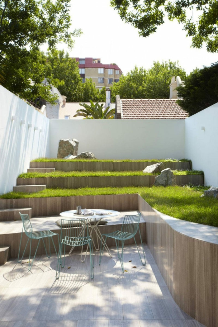 ein Garten auf Etagen mit grünem Gras, einige Gartenmöbel in blauer Farbe, Gartengestaltung Beispiele
