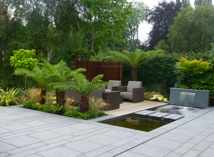 ein exotischer Garten, ein Teich voller grünes Wasser, ein Wasserspiel, drei kleine Palme und eine größere