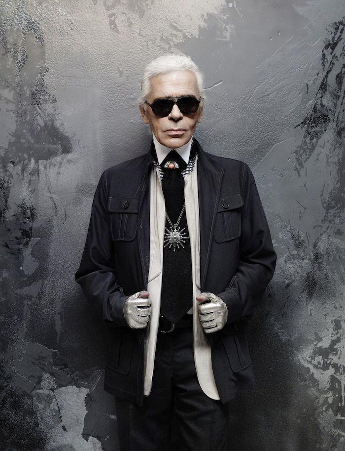 ein alter mann mit einer schwarzen sonnenbrille und schwarzem anzug und schwarzer krawatte und weißem hemd, der designer karl lagerfeld