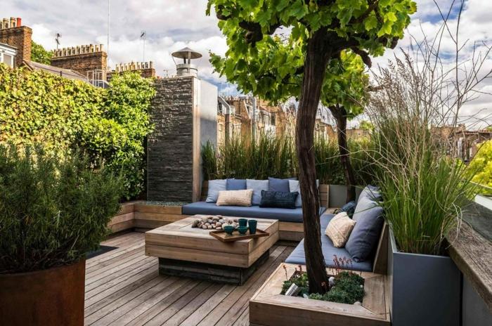 blaue Kissen, ein Tisch aus Holz, Terrassendiele, viele Bäume, ein Tischlein, Vasen, Gartengestaltung modern