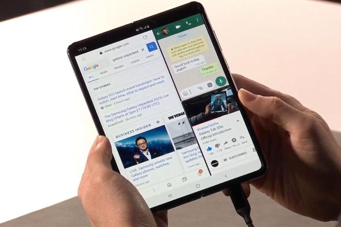 das erste faltbare Smartphone von Samsung Galaxy Fold, zwei Hände und ein schwarzes großes faltbares Smartphone mit zwei Displays