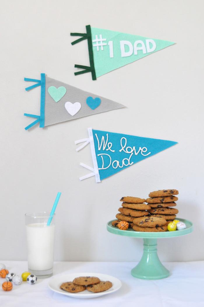 Selbstgemachte Wanddeko zum Vatertag, Dreiecke aus Filz, Kekse auf Tortenständer und Glas Milch