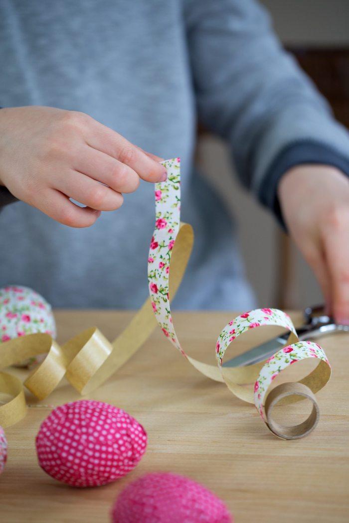 Holzeier mit kleinen Stücken Papier bekleben, Bastelidee zu Ostern für Kinder