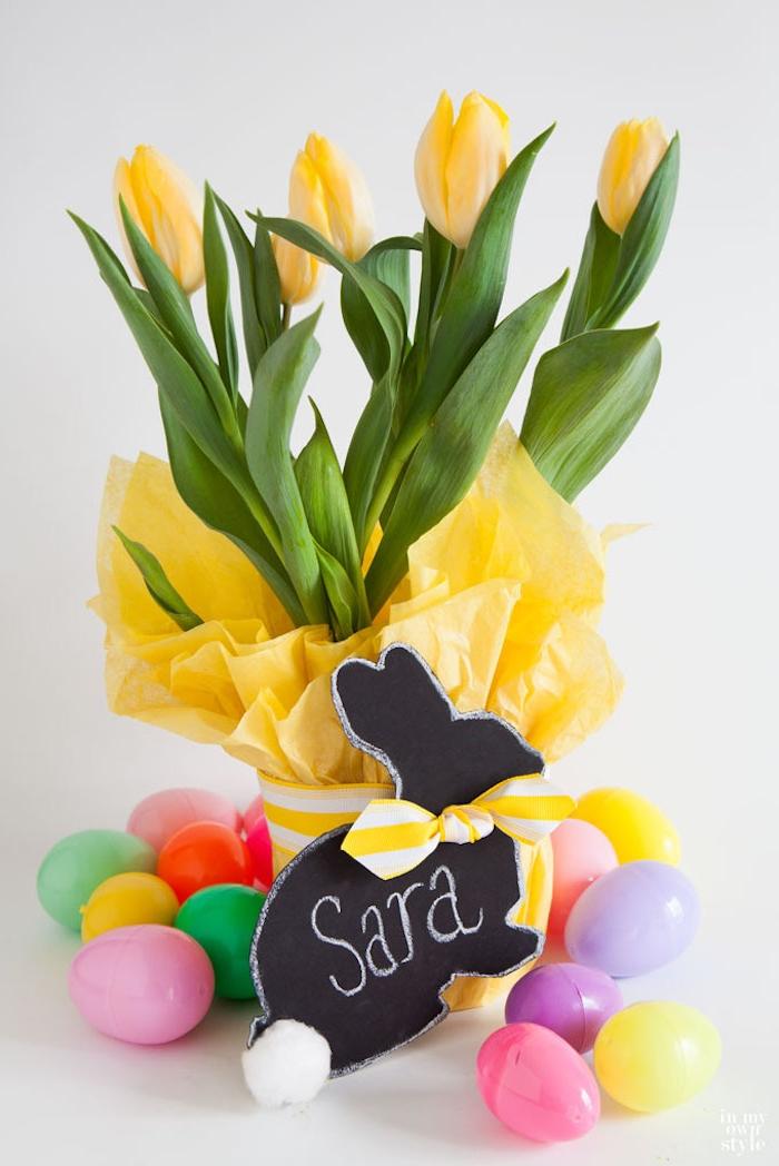 Schöne Osterdeko, bunte Plastikeier, gelbe Tulpen in Blumentopf, Osterhase aus Bastelkarton