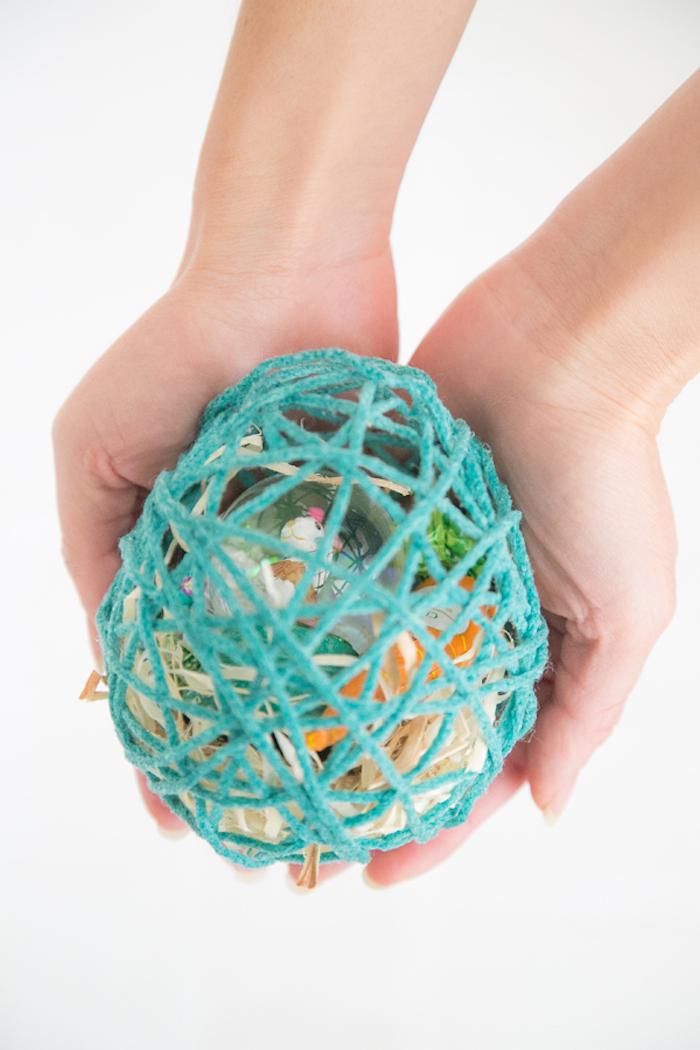 Blaues Osterei aus Garn voll mit kleinen Geschenken zu Ostern, DIY Ideen zu Ostern für Kinder