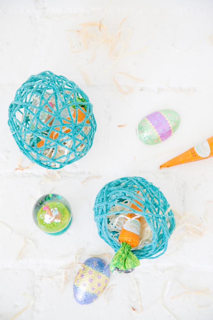 Blaue Ostereier aus Garn voll mit kleinen Süßigkeiten, DIY Idee zu Ostern für Kinder