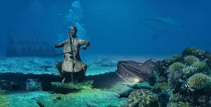 ein Bild unter Wasser, ein Haifisch in der Ferne, ein gebrochenes Auto, ein Skulptur von Mensch, der Cello spielt