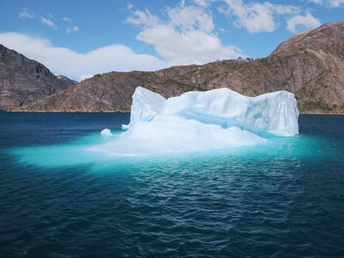 ein Eisberg zwischen in dem blauen Wasser, Gebirge in der Ferne, blaues Himmel mit weißen Wolken, schöne Profilbilder