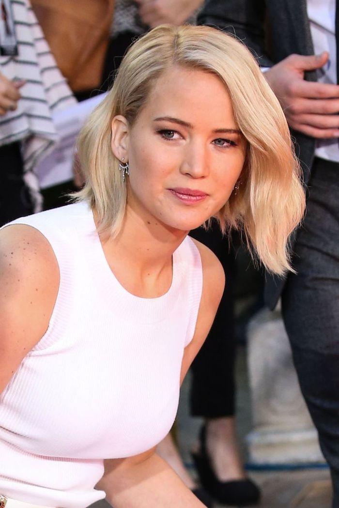 Jennifer Lawrence Haarschnitt, Bob mit Seitenscheitel, blonde wellige Haare, weißes Outfit