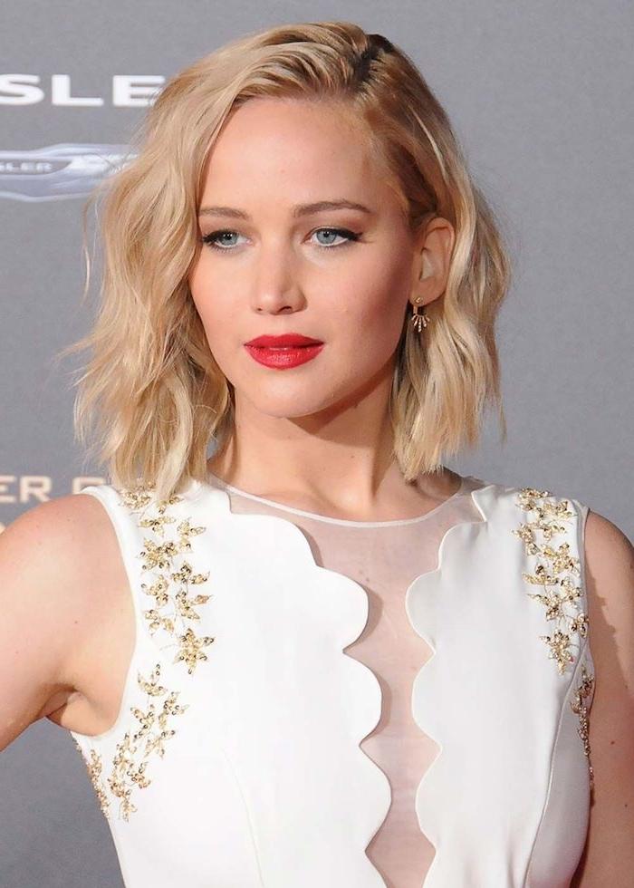 Jennifer Lawrence Bob Haarschnitt mit Seitenscheitel, blonde wellige Haare, weißes Kleid, schwarzer Lidstrich und roter Lippenstift