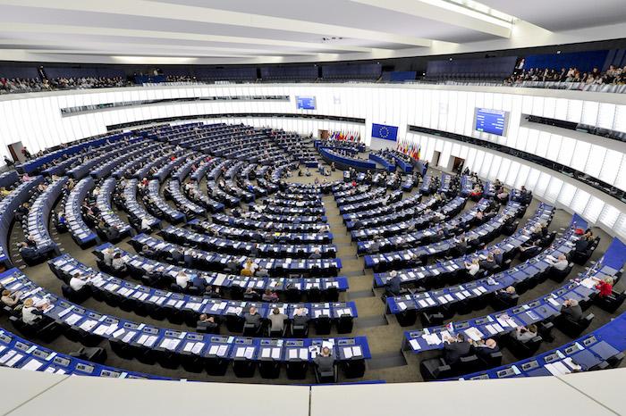das parlament der europäischen union, viele menschen und blaue schreibtische und stähle und weiße wände