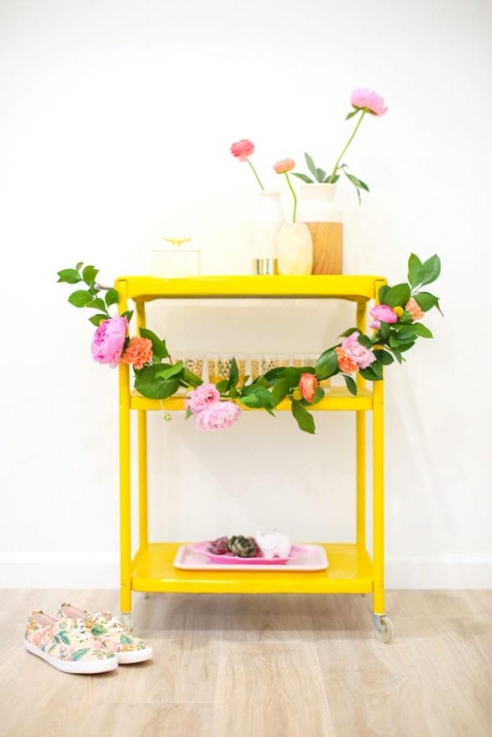 gelber tisch dekoriert mit girlande aus grünen blättern und frühlingsblumen, deko ideen selbst machen
