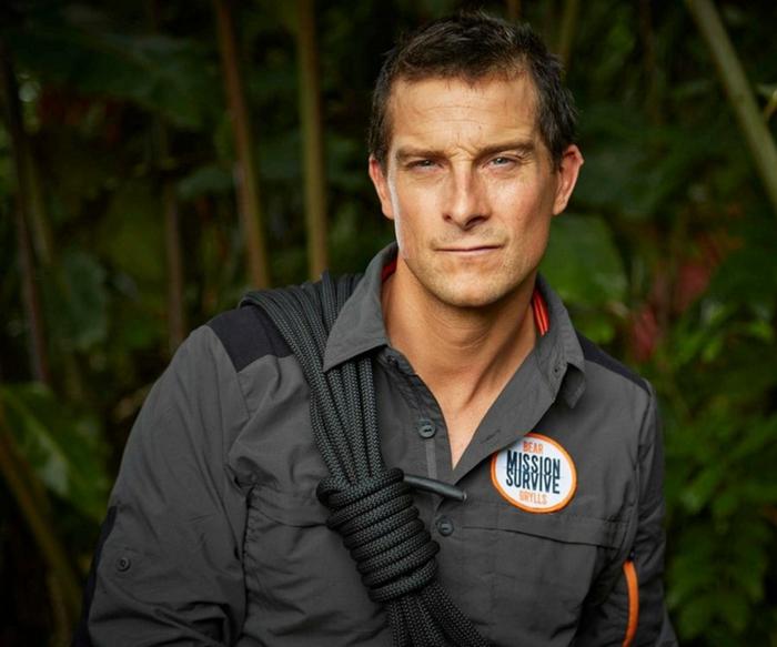 Bear Grylls, ein schwarzes Hemd, ein Aufkleber mit Aufschrift Mission Survive