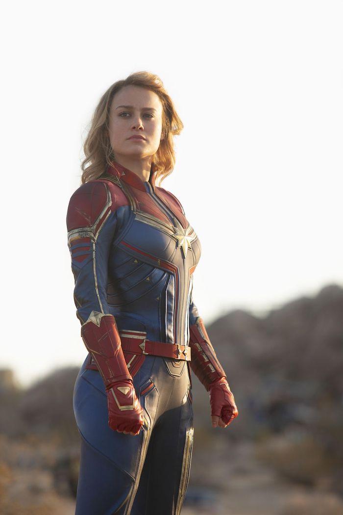 captain marvel, die schauspielerin brie larson mit einem blau roten superhelden kostüm mit einem gelben großen stern