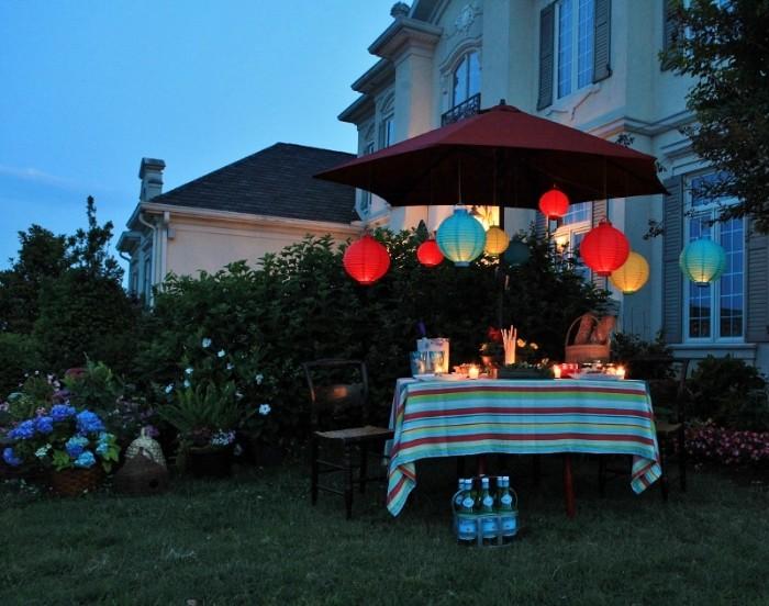 dekorationen für den garten, die gartenhäuser ersetzen können, tisch mit sonnenschirm und schöne party deko, leuchten und kerzen, geburtstagsparty gartenparty