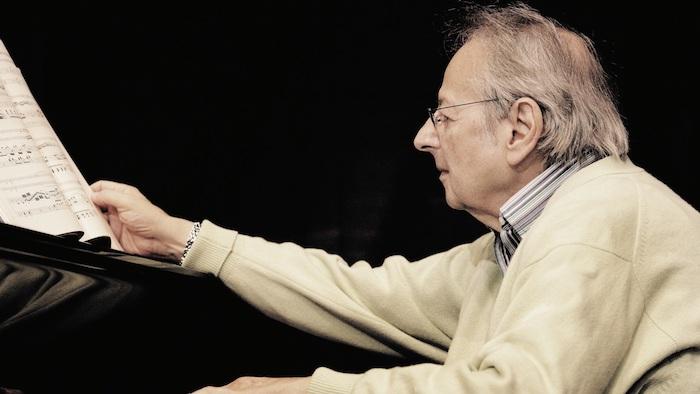 alter mann mit einer grauen armbanduhr und einer brille, ein buch und piano, der pianist André Previn