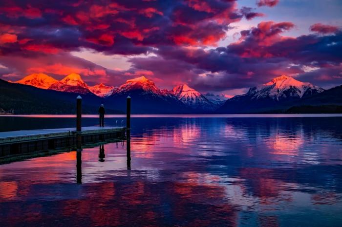 Gebirge beim Sonnenuntergang, hohe Gebirge mit roten Bergen, ein See mit Kai, eine Menschenfigur, unique Bilder