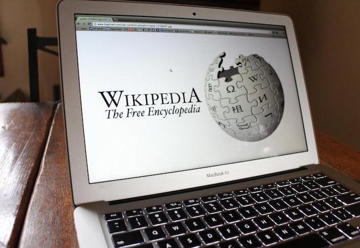 ein laptop mit einem bildschirm mit der startseite von wikipedia mit dem weißen modularen globus, der logo von wikipedia