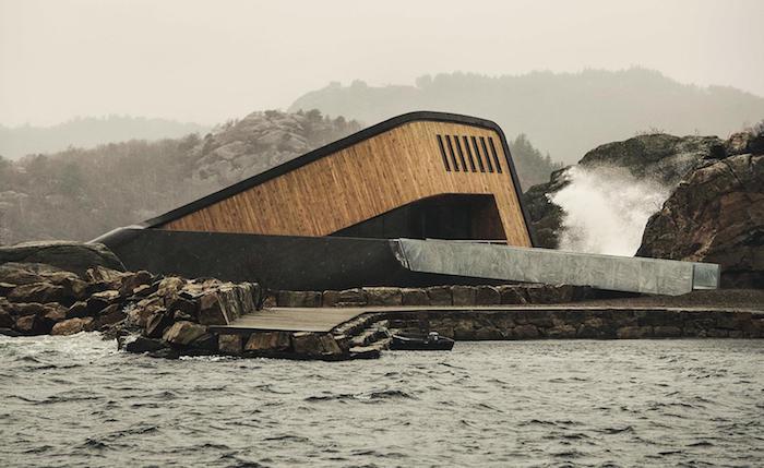 meer mit großen wellen, küste mit steinen und ein unterwasser restaurant aus holz und beton