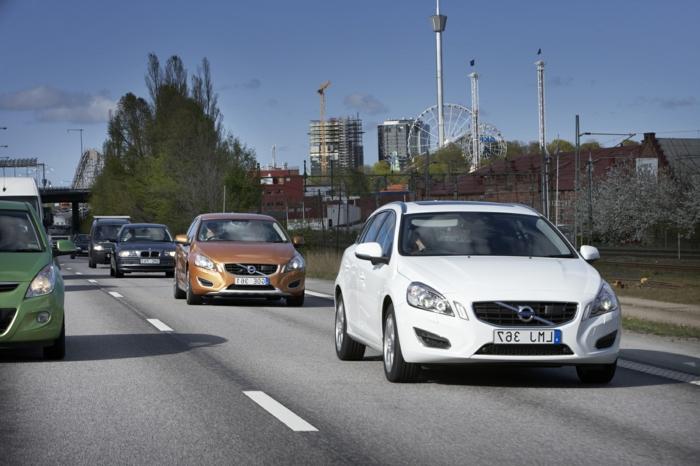einige Autos auf der Autobahn, eine Reihe von Volvos in weißer, goldener, grüner und schwarzer Farbe