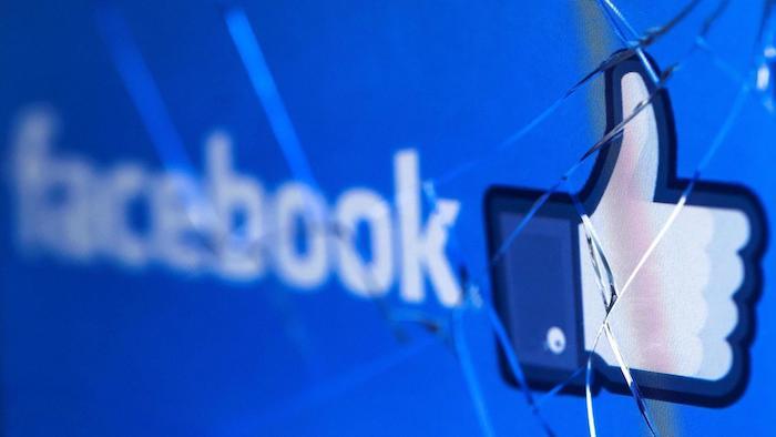 der logo von dem sozialen netzwerk facebook, ein gebrochener bildschirm eines laptops, eine kleine weiße hand