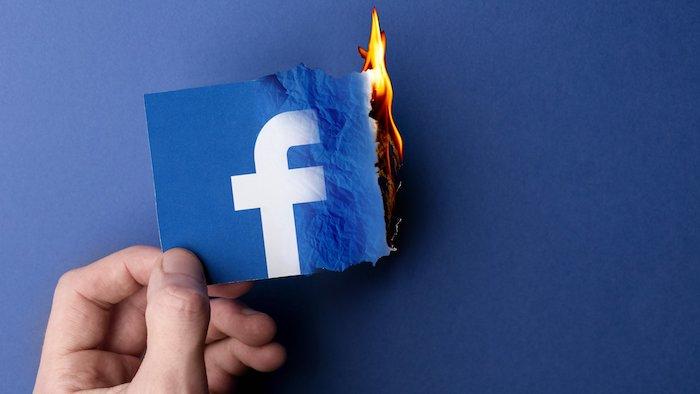 feuer und der brennender logo von dem sozialen plattform facebook, eine hand und ein blauer tisch