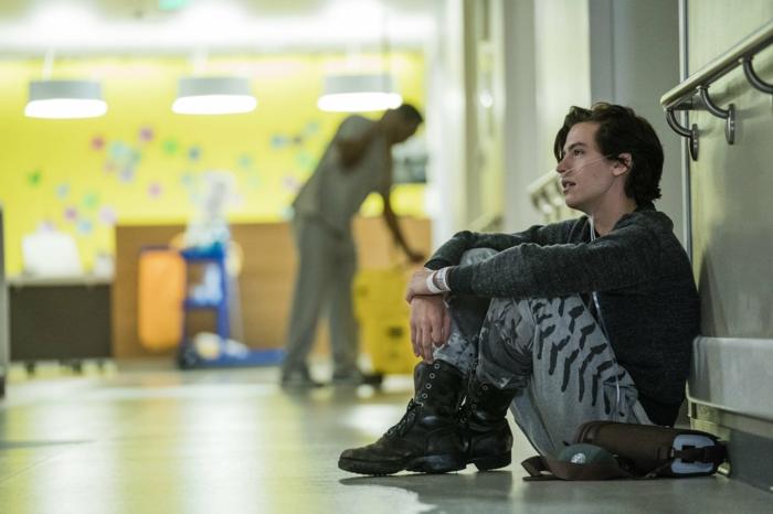 der junge Mann sitzt im Krankenhaus auf dem Boden mit Atemhilfe