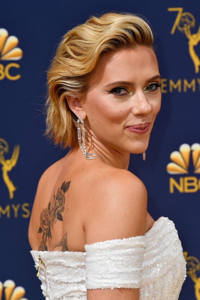 Kurzhaarfrisuren für Frauen, blonde wellige Haare kinnlang, weißes schulterfreies Kleid, Rosen Tattoo am Rücken