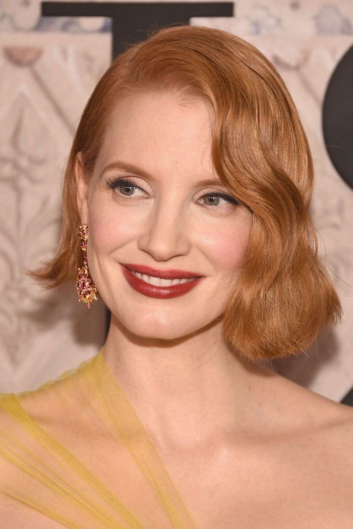 Asymmetrischer Bob Haarschnitt, Haarfarbe Kupferrot, roter Lippenstift, gelbes Kleid