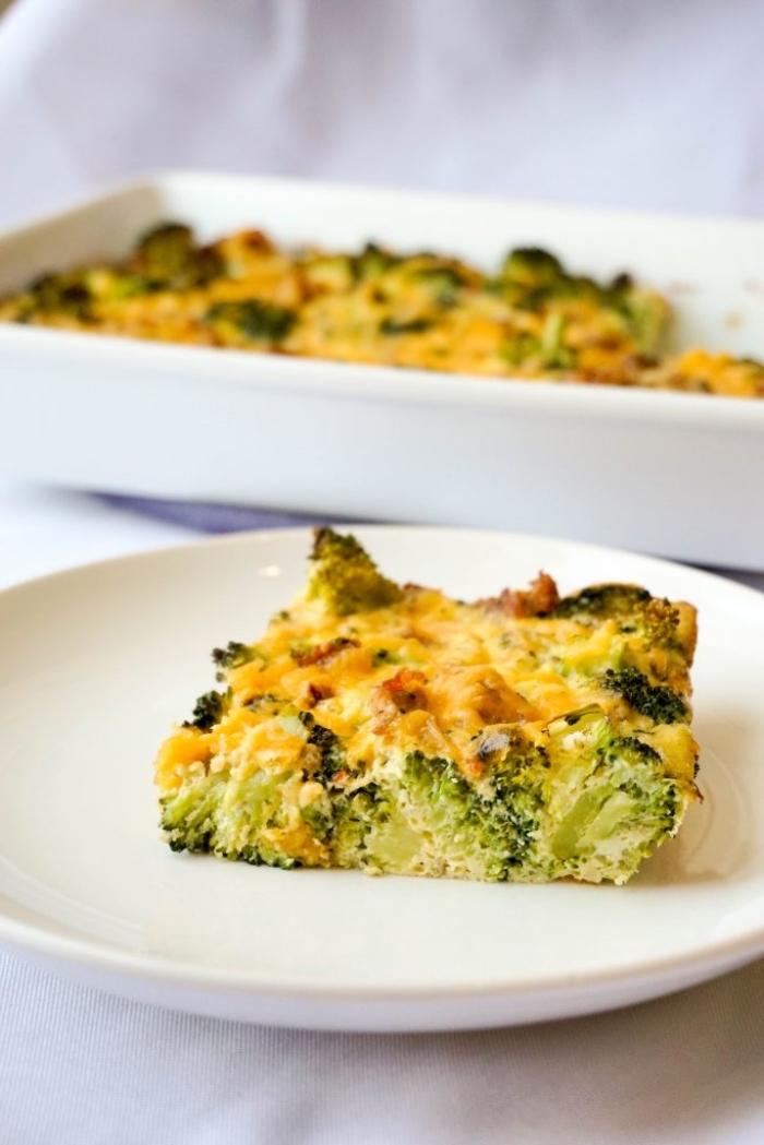 frühstück ohne kohlenhydrate, kasserolle mit eier, käse und brokkoli, stück chneiden, weißer teller
