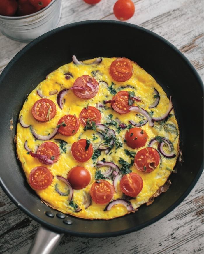 frühstück ohne kohlenhydrate, schwarze pfanne, omelette mit cherry tomaten, zwiebel und petersillie