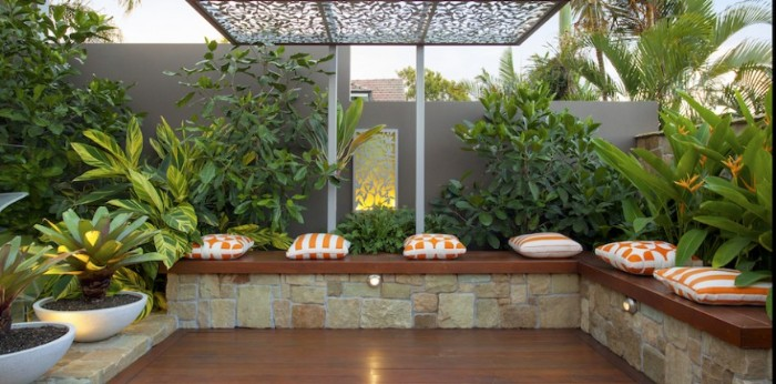 Design Gartenhaus Idee, lange Sitzbank mit rechtem Eck und viele flauschige Sitzkissen, Pflanzen, Ort zum Treffen, Sauna im Garten
