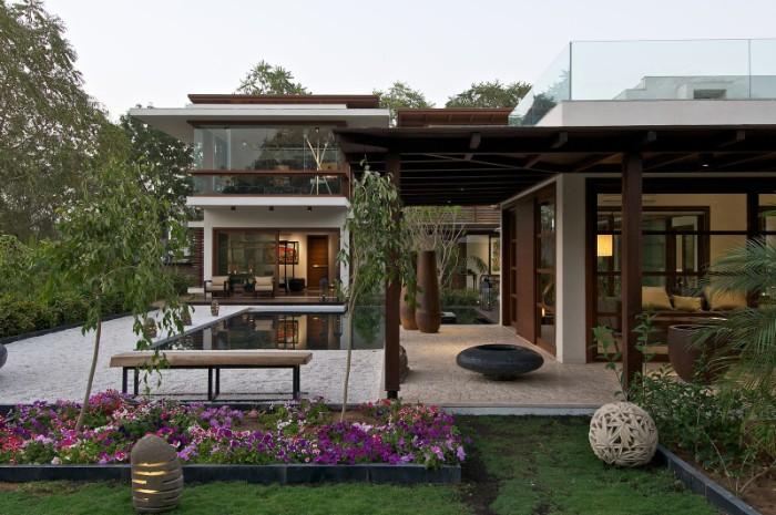 Gartenhaus Holz Flachdach, schöne Blumen in lila Farbe, Bepflanzung, kleiner Pool