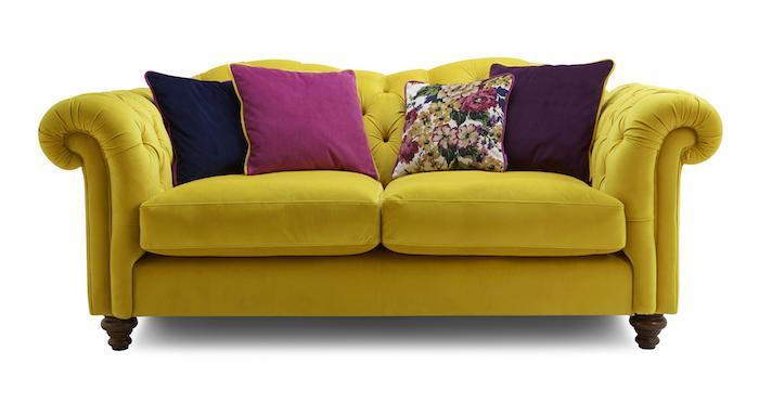ein gelbes sofa und vier bunte kissen