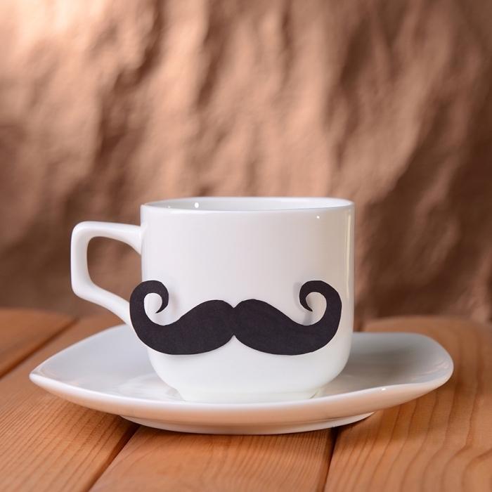 DIY Geschenkidee zum Vatertag, weiße Porzellantasse mit Schnurrbart aus schwarzem Tonkarton