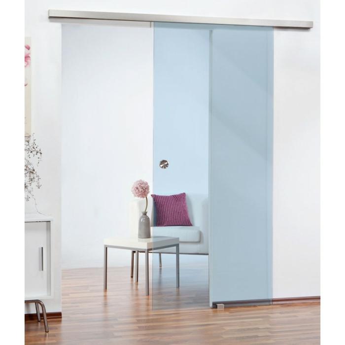 eine Glasschiebetür in blauer Farbe, Laminatboden, ein Sofa in weißer Farbe und ein rosa Kissen