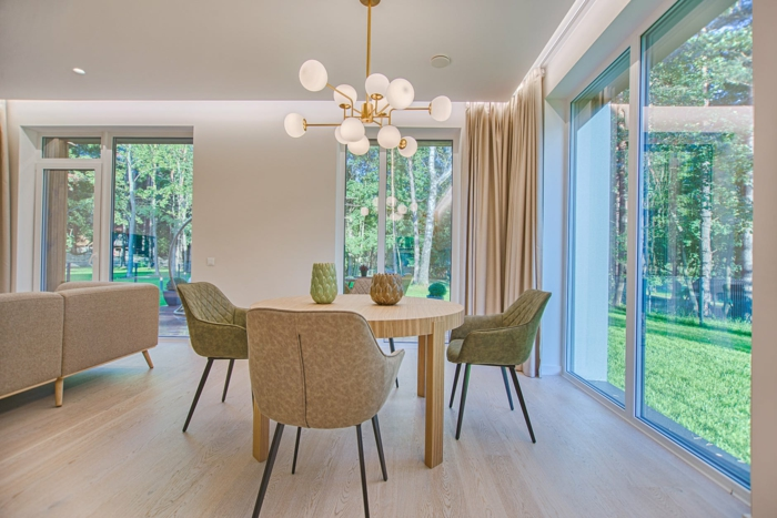 ein Tisch mit drei Stühle, eine Lampe, ein Laminatboden, moderne Glasschiebetüren
